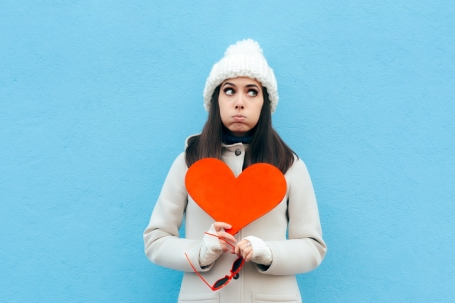 Heartbroken Sad Upset Girl Holding a Heart on Blue Background