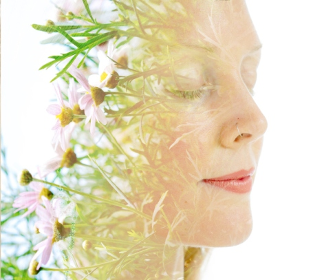 Double exposure of a young, happy woman's profile combined with beautiful delicate pink flowers